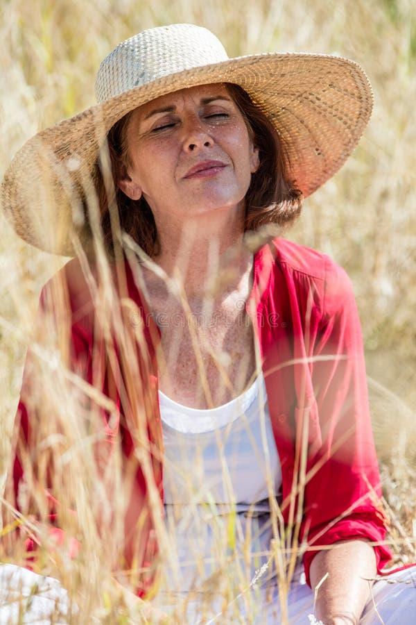Mulher mais idosa bonita de sorriso que aprecia o sol no campo seco alto do verão imagens de stock
