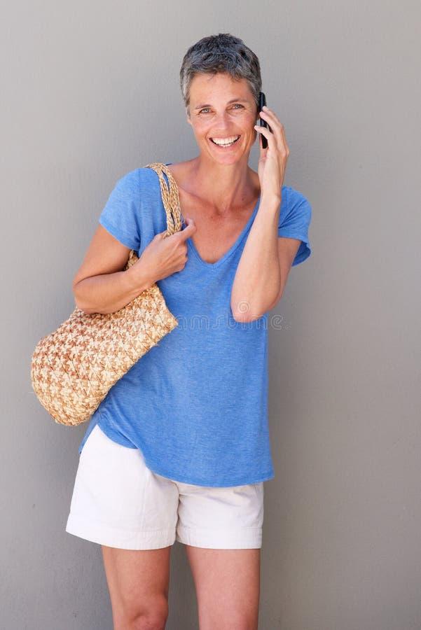 Mulher mais idosa bonita de sorriso que fala no telefone celular fotografia de stock