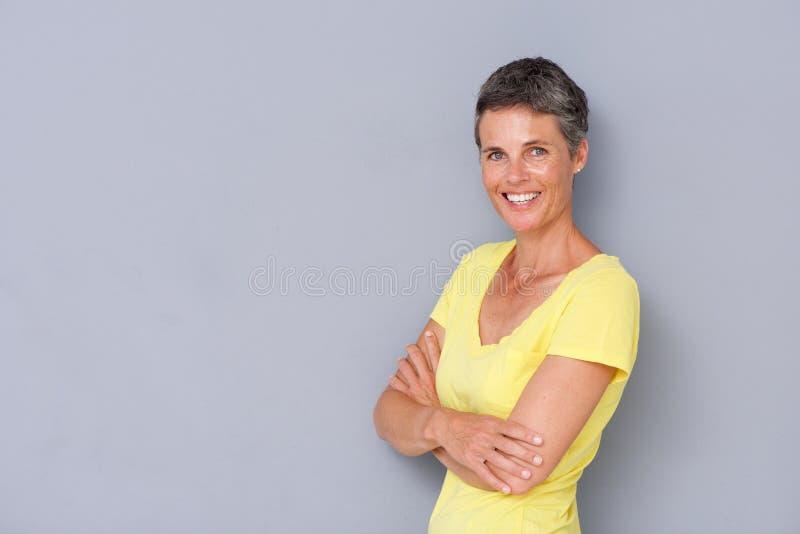 Mulher mais idosa bonita que sorri contra o fundo cinzento fotos de stock royalty free
