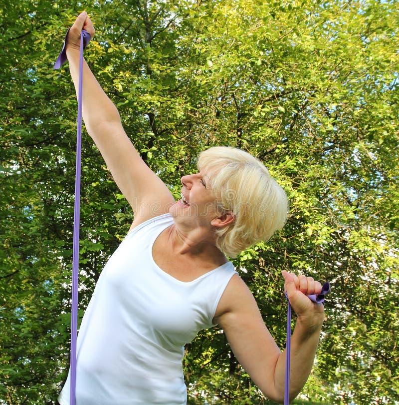 Mulher mais idosa com a faixa da aptidão na natureza imagem de stock royalty free