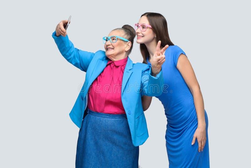 Mulher mais idosa com a neta que faz o selfie e o sorriso toothy foto de stock royalty free