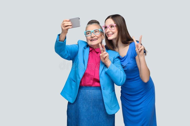 Mulher mais idosa com o neto que faz o selfie e o sorriso toothy fotografia de stock