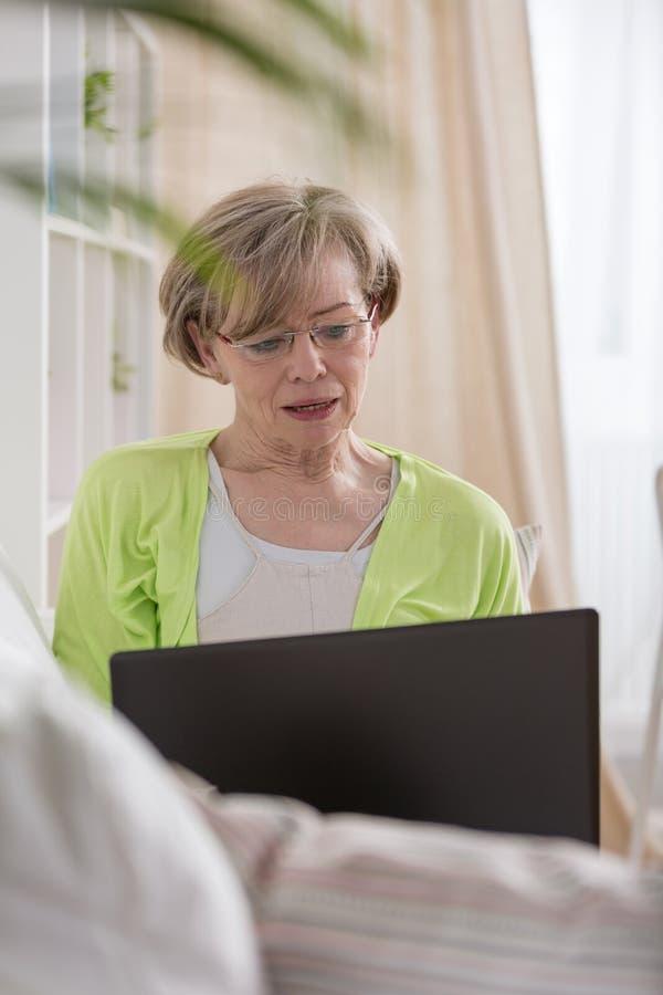 Mulher mais idosa com portátil imagens de stock