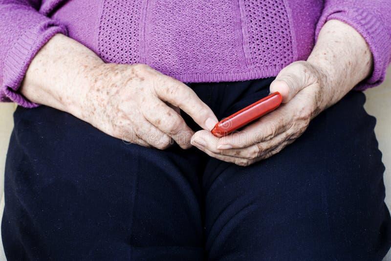 Mulher mais idosa com um smartphone imagens de stock