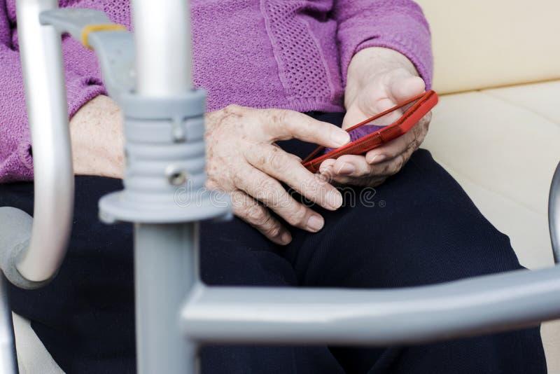 Mulher mais idosa com um smartphone e um caminhante ortopédico imagens de stock