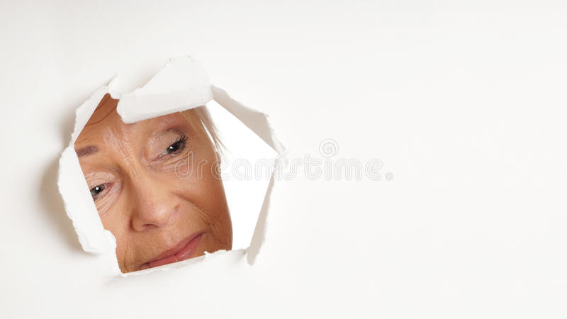 Mulher mais idosa curiosa que olha através do furo no espaço da cópia fotografia de stock