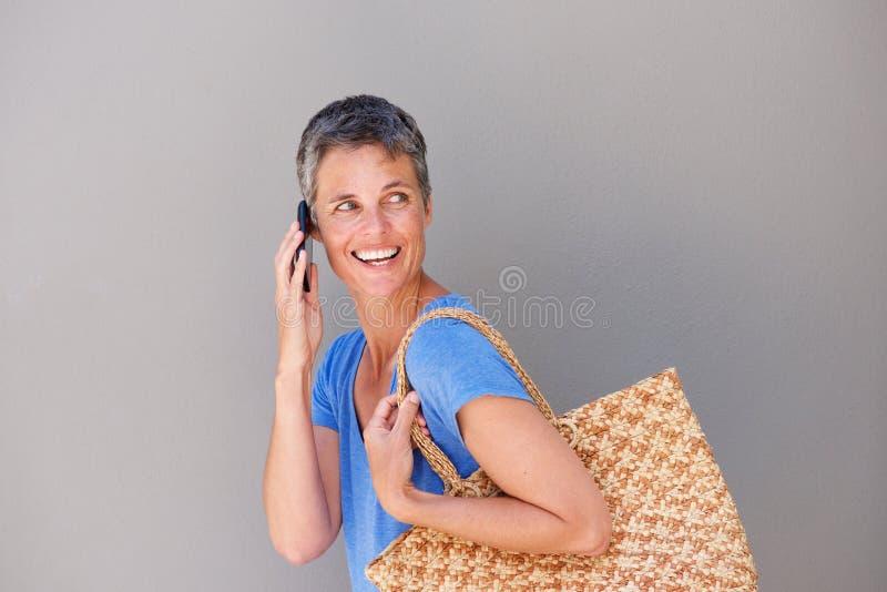 Mulher mais idosa de sorriso que anda e que fala no telefone celular foto de stock