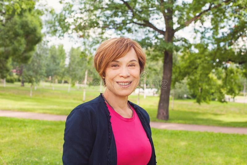 Mulher mais idosa de sorriso que anda no parque Mulher idosa com ar livre curto vermelho do corte de cabelo Beleza madura fotos de stock royalty free