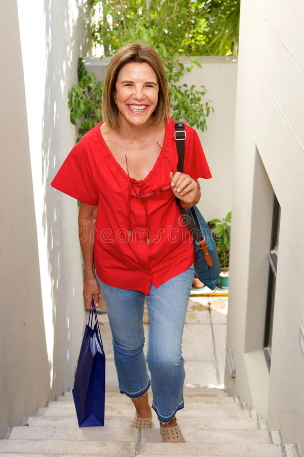 Mulher mais idosa feliz que anda acima das etapas com saco fotos de stock