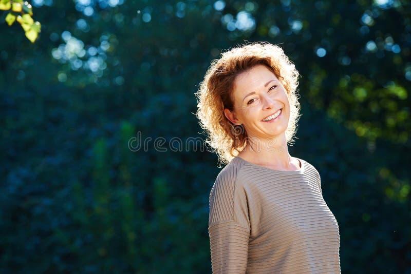 Mulher mais idosa feliz que está no parque tranquilo fotos de stock
