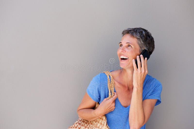 Mulher mais idosa feliz que fala no telefone celular fotografia de stock