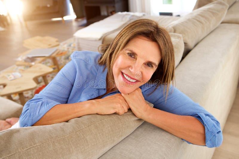 Mulher mais idosa feliz que relaxa em casa no sofá imagem de stock royalty free
