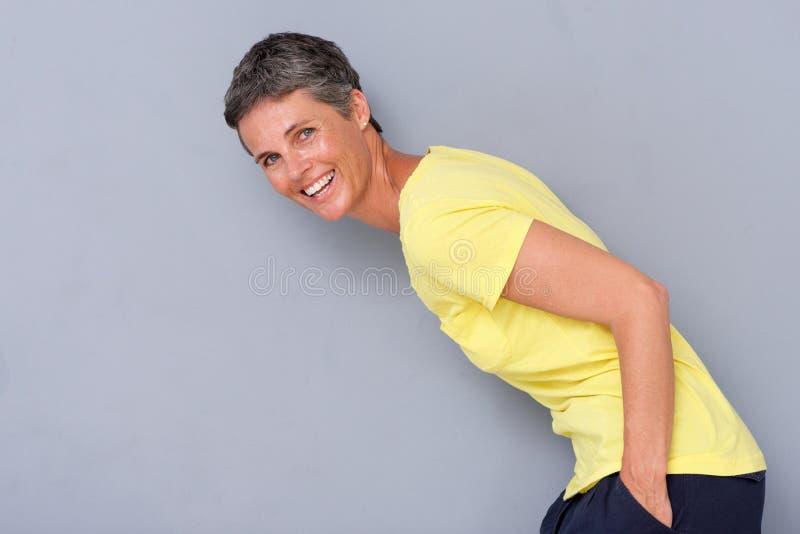 Mulher mais idosa feliz que ri contra o fundo cinzento fotos de stock