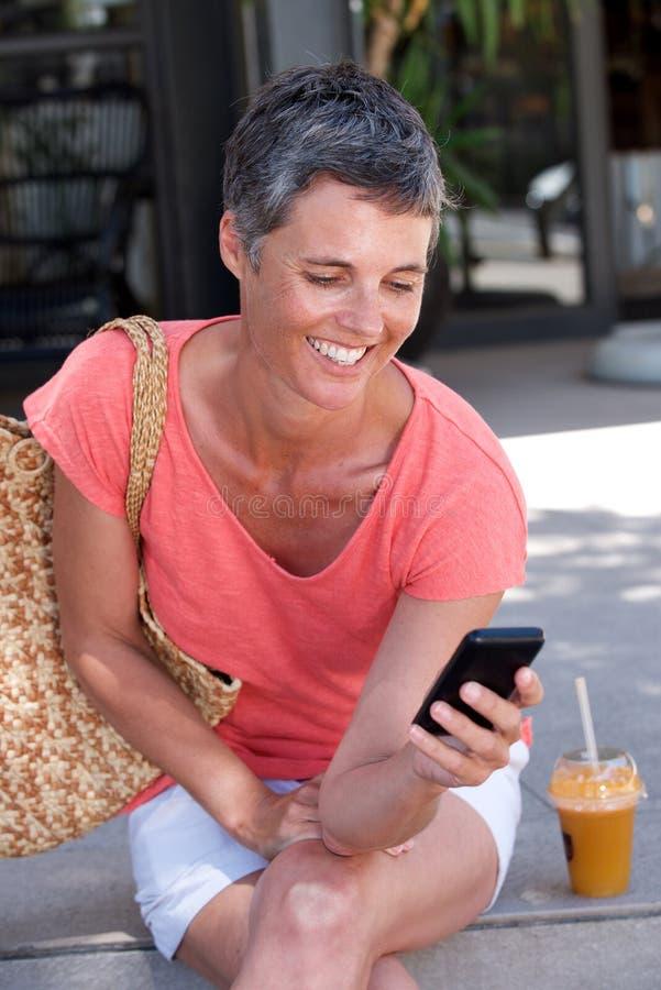 Mulher mais idosa feliz que senta-se fora com bebida e que usa o telefone celular fotos de stock royalty free