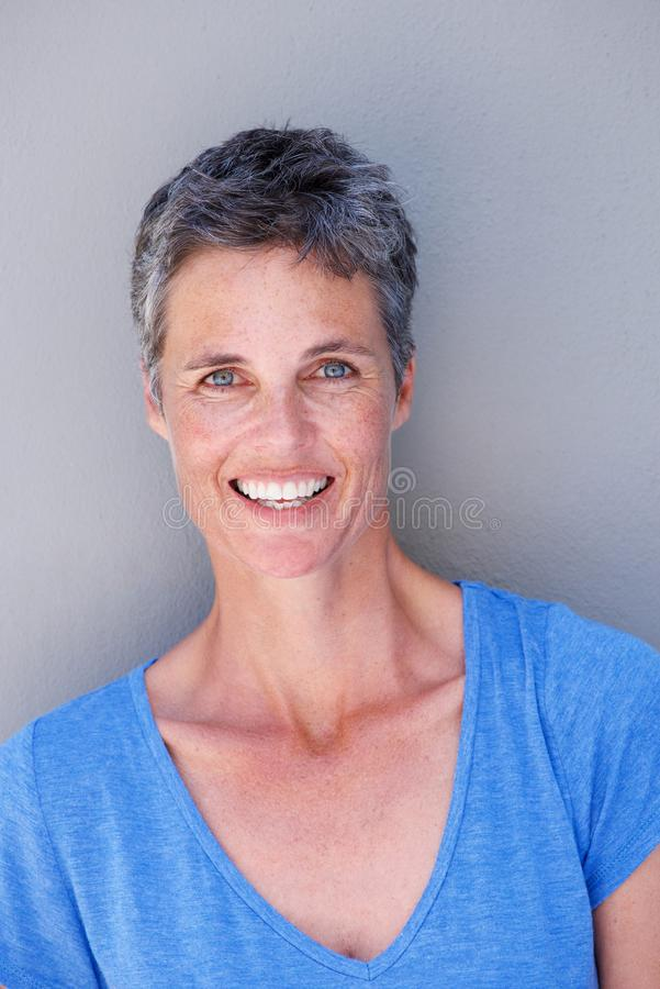 Mulher mais idosa feliz que sorri contra o fundo cinzento imagem de stock royalty free