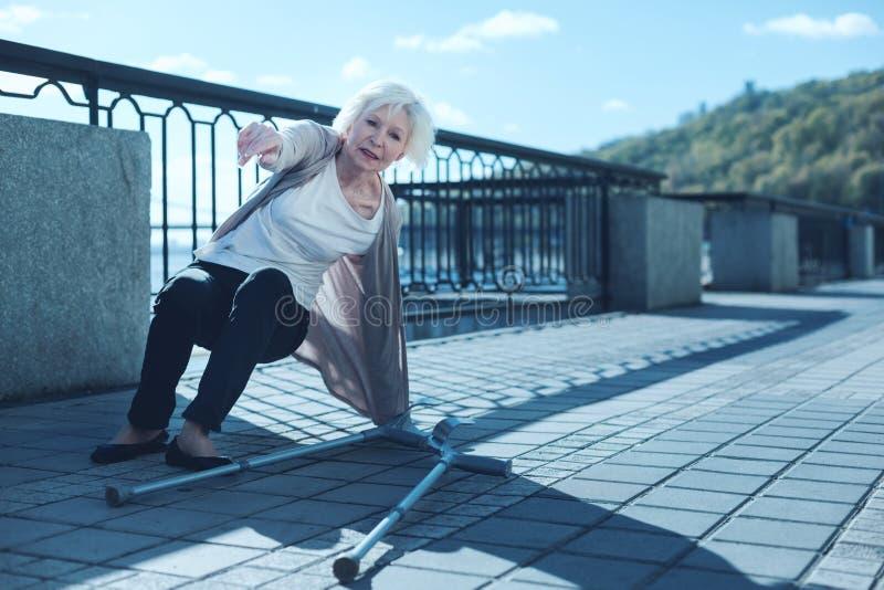 Mulher mais idosa fisicamente esgotada que levanta-se após a queda com muletas fotografia de stock royalty free