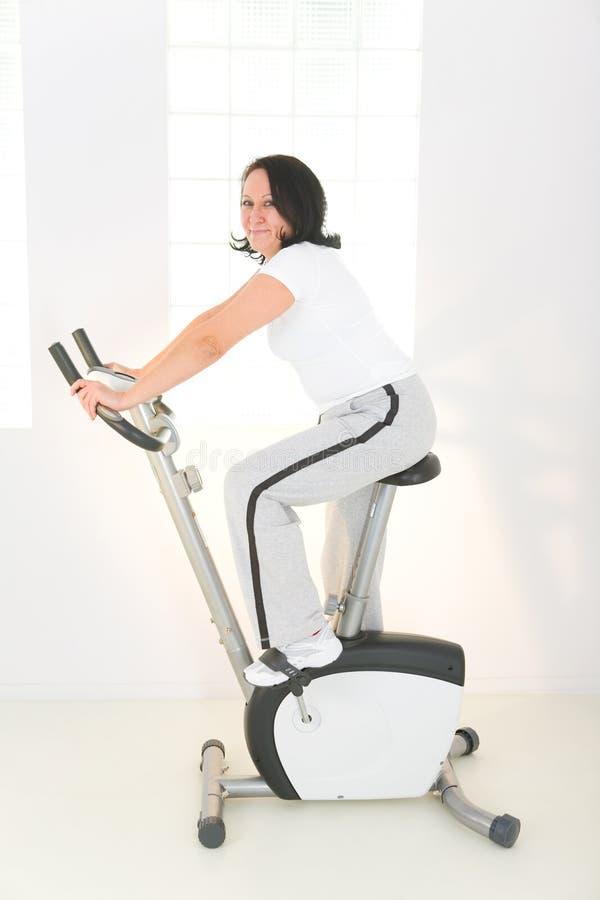 Mulher mais idosa na bicicleta de exercício imagens de stock