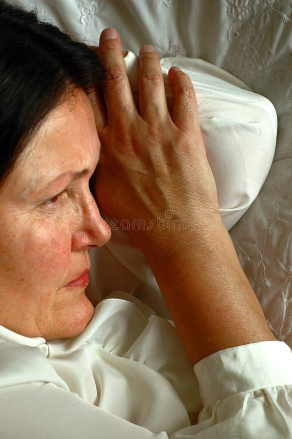 Mulher mais idosa que aflige-se na cama fotos de stock