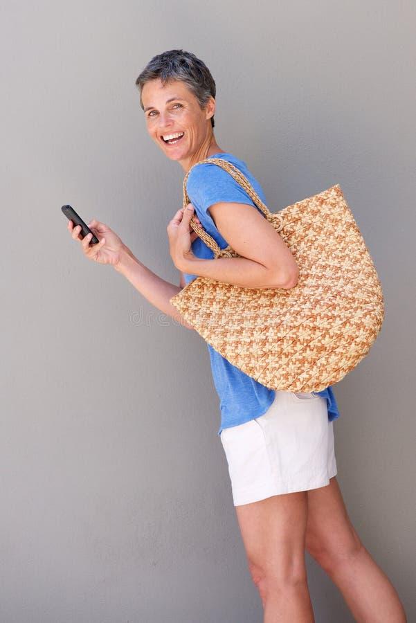 Mulher mais idosa que anda com saco e telefone celular imagem de stock royalty free