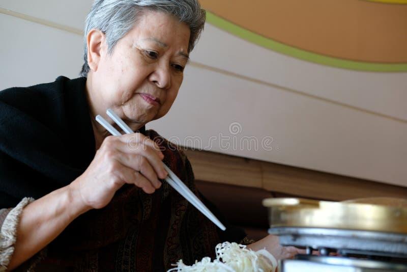 mulher mais idosa idosa idosa que come o alimento no restaurante o mais lifest superior foto de stock