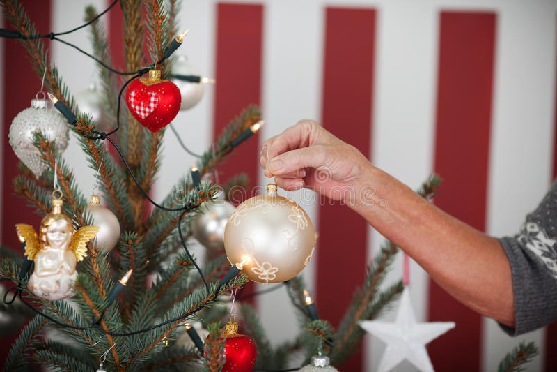 Mulher mais idosa que decora uma árvore de Natal imagem de stock royalty free