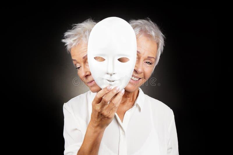 Mulher mais idosa que esconde a cara feliz e triste atrás da máscara fotos de stock royalty free