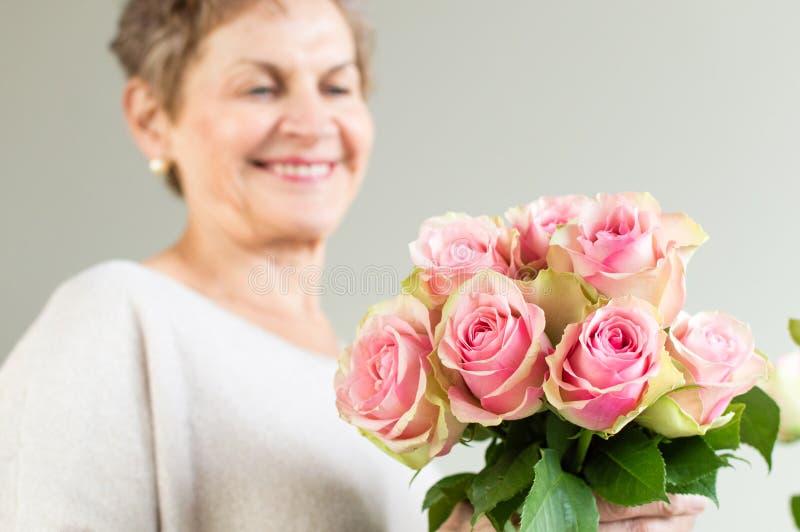 Mulher mais idosa que guarda rosas foto de stock