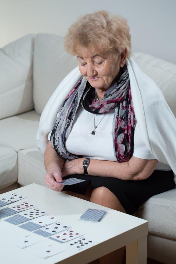 Mulher mais idosa que joga o solitário foto de stock