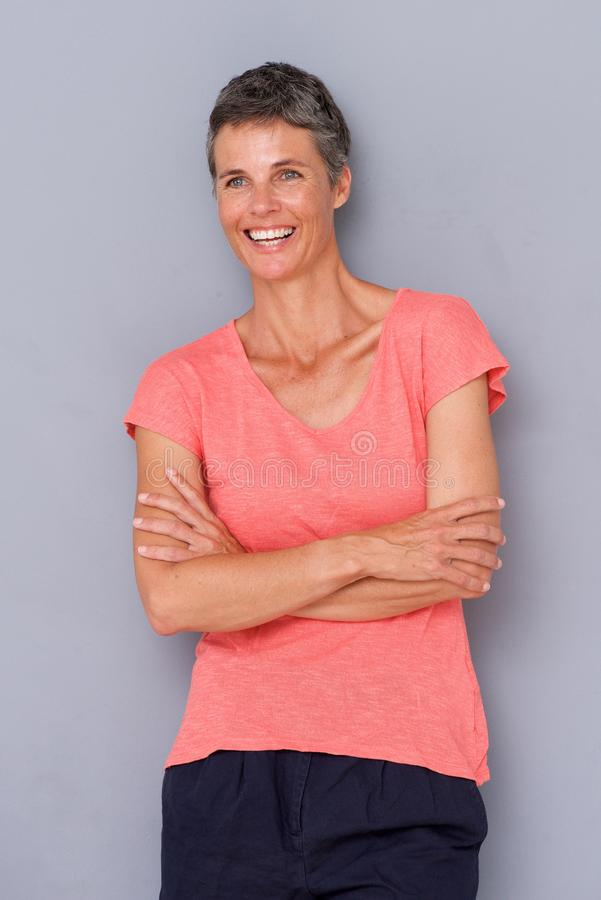 Mulher mais idosa relaxado que sorri pela parede cinzenta imagens de stock royalty free