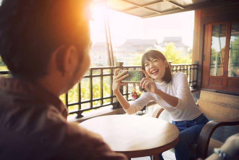 Mulher mais nova do asiático alegre bonito que toma uma foto pelo telefone esperto com emoção da felicidade fotos de stock royalty free