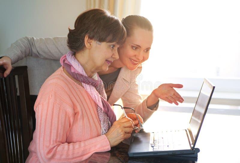 Mulher mais nova que ajuda uma pessoa idosa que usa o laptop para a busca do Internet Jovens e gerações da idade da reforma que t fotografia de stock