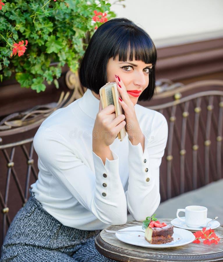 A mulher manda a bebida apreciar ler o bom terraço do café do livro Literatura moderna para a fêmea A senhora do negócio leu o li fotos de stock royalty free