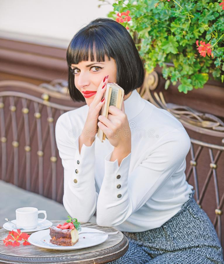 A mulher manda a bebida apreciar ler o bom terraço do café do livro Literatura moderna para a fêmea A senhora do negócio leu o li fotografia de stock