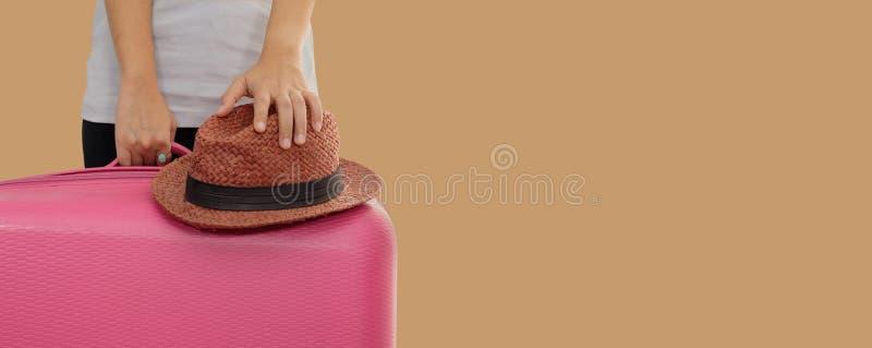 A mulher mantém a mala de viagem isolada no fundo marrom com spac da cópia imagem de stock