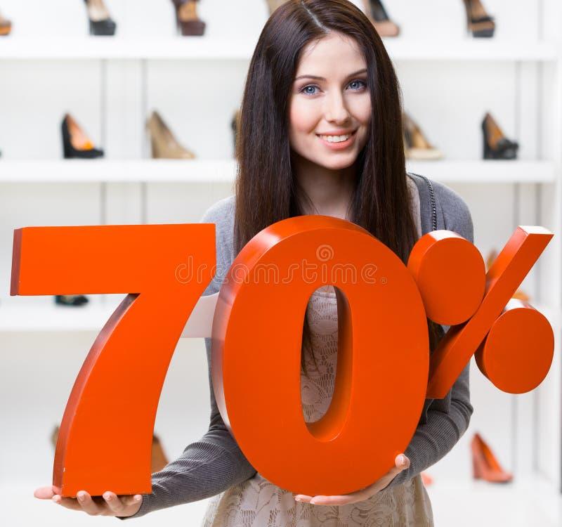 A mulher mantém o modelo da venda de 70% em calçados fotos de stock royalty free