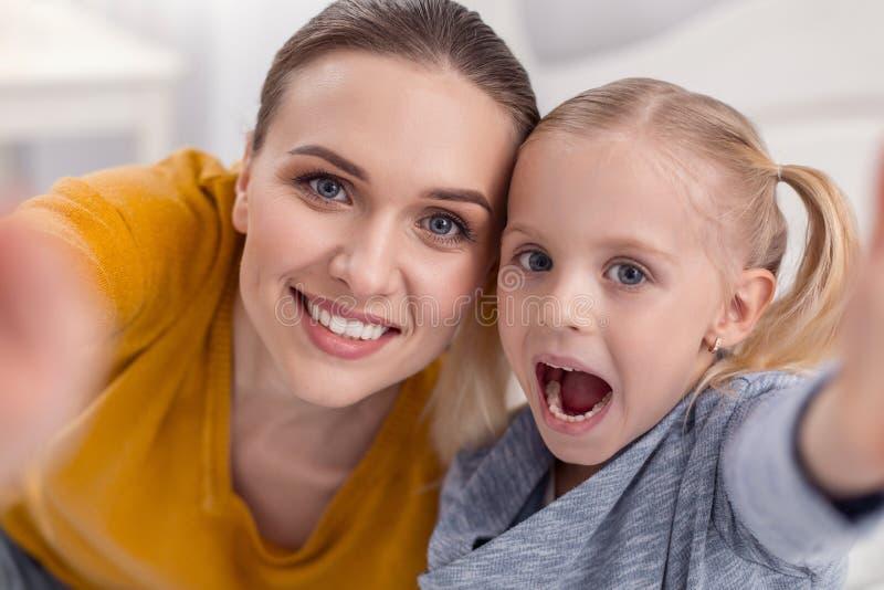 Mulher maravilhosa e menina felizes que fazem o divertimento foto de stock royalty free
