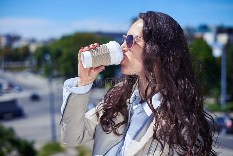 Mulher maravilhosa que aprecia o panorama da cidade e que bebe o café foto de stock