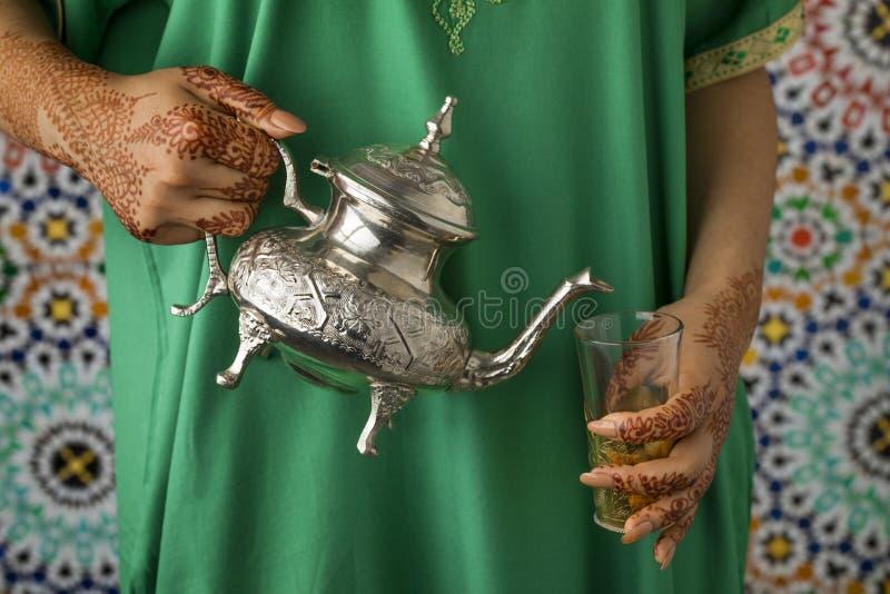 A mulher marroquina com hena pintou as mãos que derramam o chá fotografia de stock royalty free