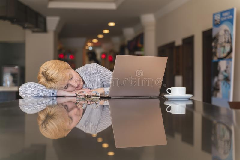 Mulher menopáusica no trabalho sente mal, depressão de força e tem um descanso Ela dorme no local de trabalho antes do laptop à m fotografia de stock