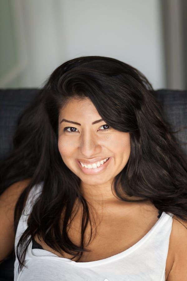 Mulher mexicana nova que sorri e que relaxa em um sofá HOME foto de stock