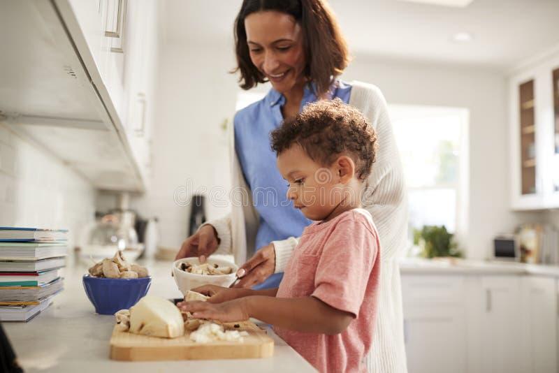 Mulher milenar e seu filho da criança que preparam o alimento que levanta-se junto em um worktop na cozinha, vista lateral, fim,  imagem de stock