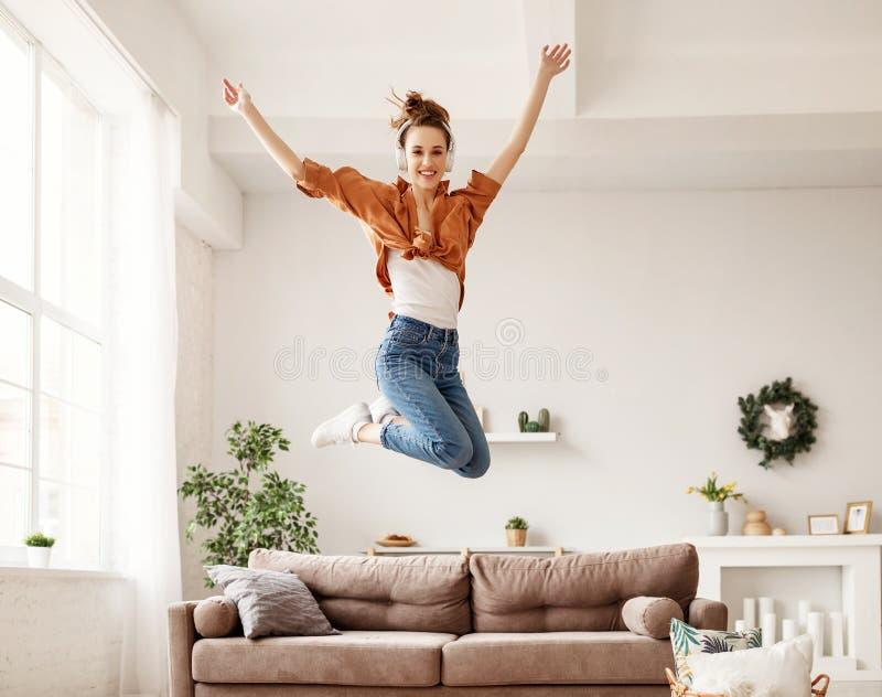 Mulher milenar empolgada ouvindo música e tendo chiclete em casa imagem de stock royalty free