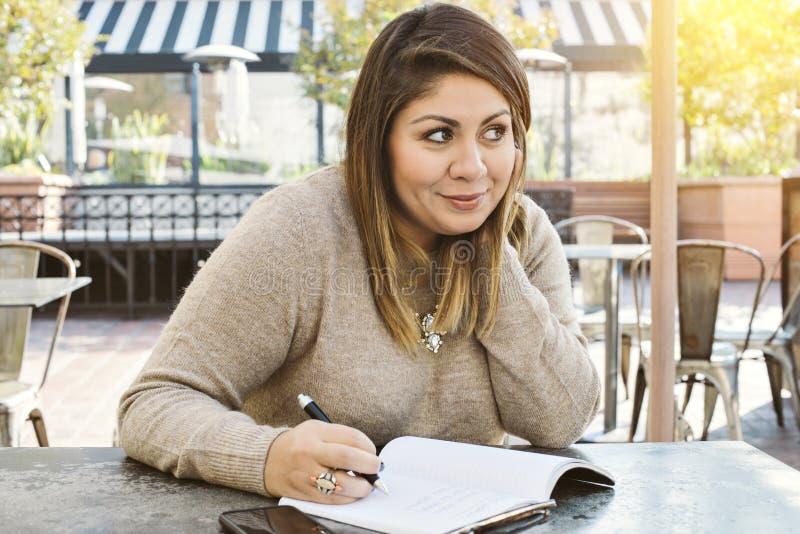 A mulher milenar escreve para baixo seus objetivos da vida em um café exterior com iluminação morna imagens de stock royalty free