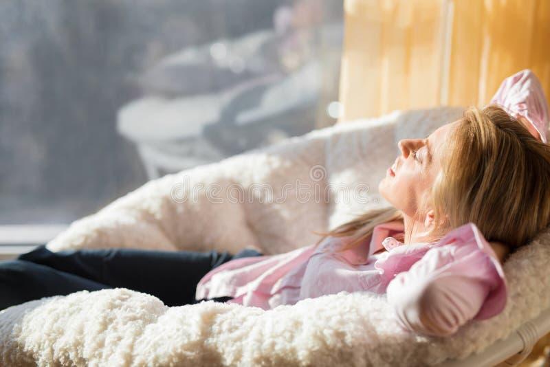 Mulher mimada que relaxa na cadeira imagem de stock royalty free