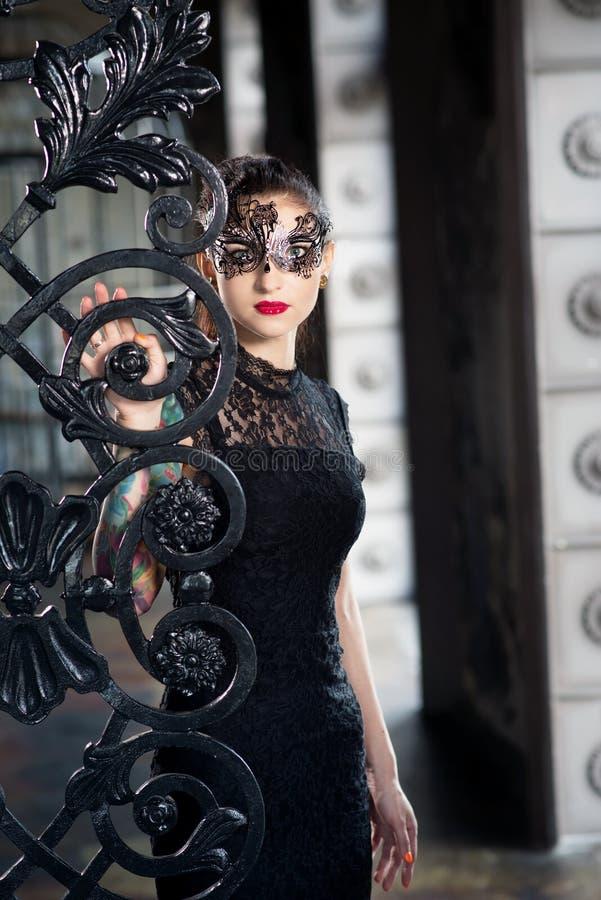 Mulher misteriosa na máscara venetian do carnaval perto da porta do ferro forjado fotografia de stock royalty free