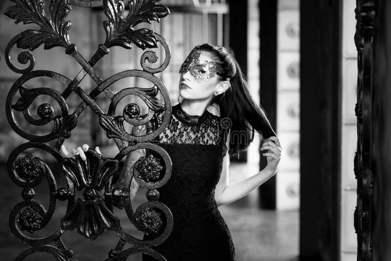 Mulher misteriosa na máscara venetian do carnaval perto da porta do ferro forjado Estilo Noir imagem de stock royalty free