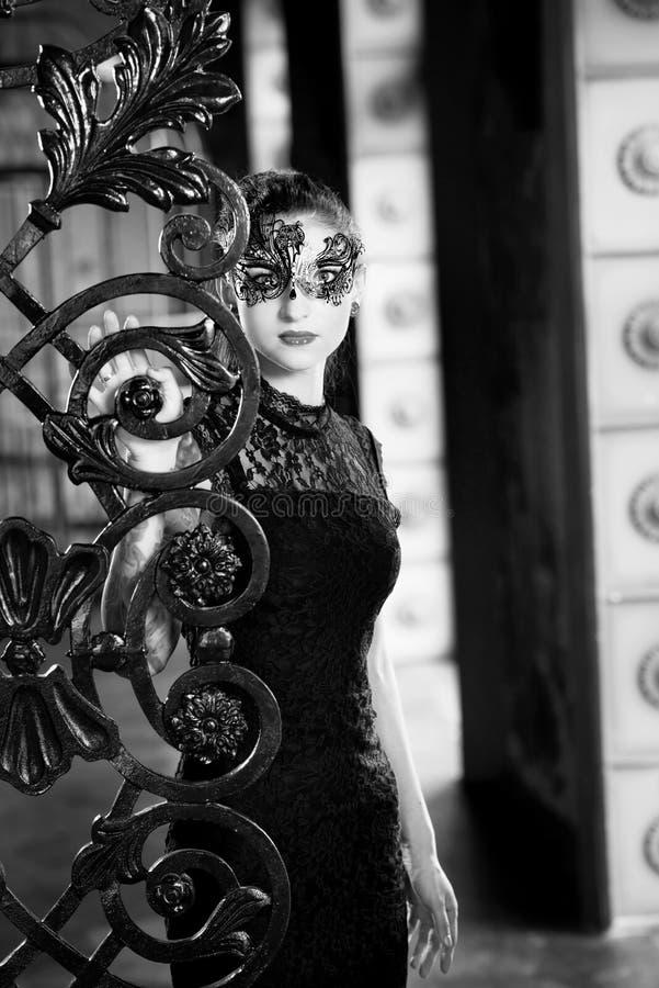 Mulher misteriosa na máscara venetian do carnaval perto da porta do ferro forjado Estilo Noir fotos de stock