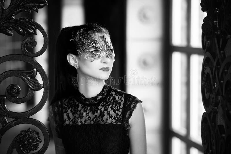 Mulher misteriosa na máscara venetian do carnaval perto da porta do ferro forjado Estilo Noir fotografia de stock royalty free