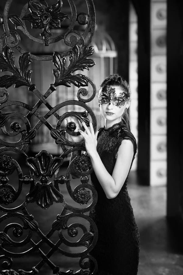 Mulher misteriosa na máscara venetian do carnaval perto da porta do ferro forjado Estilo Noir fotos de stock royalty free