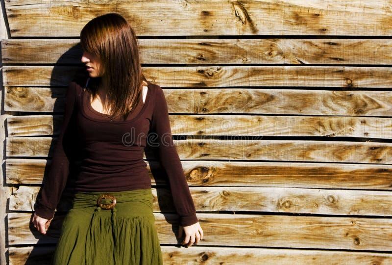 Mulher misteriosa na parede de madeira fotografia de stock